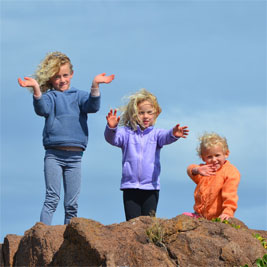 Three Kids standing on a rock