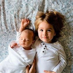 titelbild elterngeld-news, geschwisterkinder liegen nebeneinander im bett
