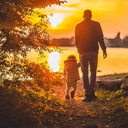 Father and child at sunset at the lake